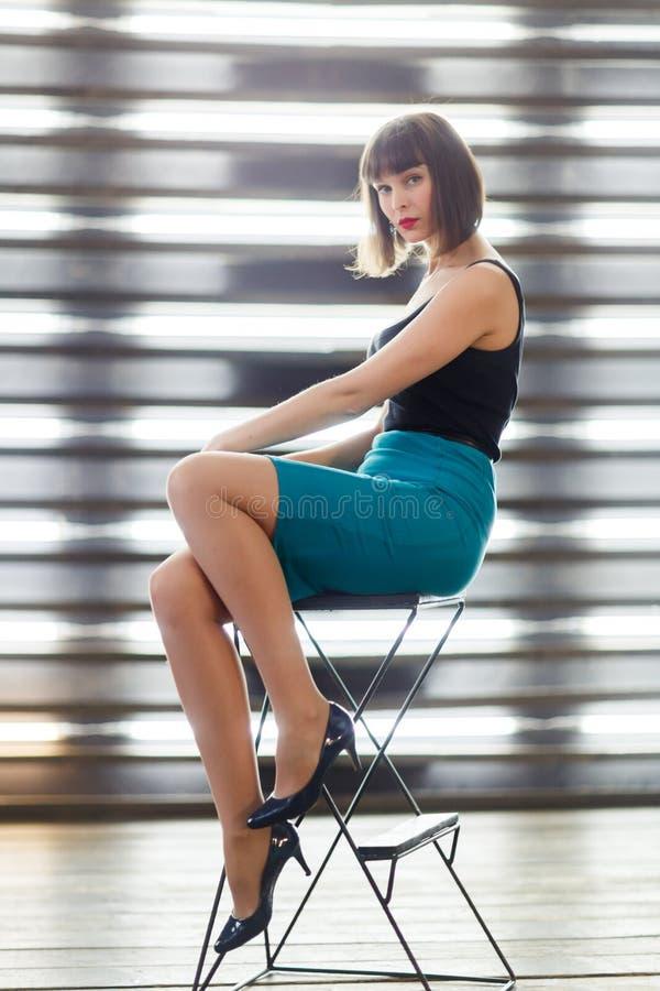 Foto de la morenita joven que se sienta en silla cerca de ventana con las persianas fotos de archivo