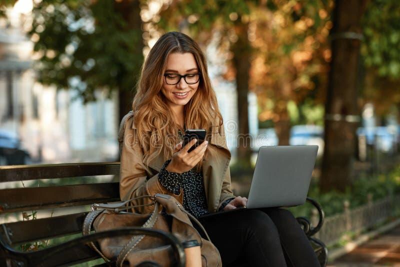 Foto de la muchacha caucásica que usa el teléfono móvil y el ordenador portátil mientras que se sienta en banco en callejón ilumi imagenes de archivo