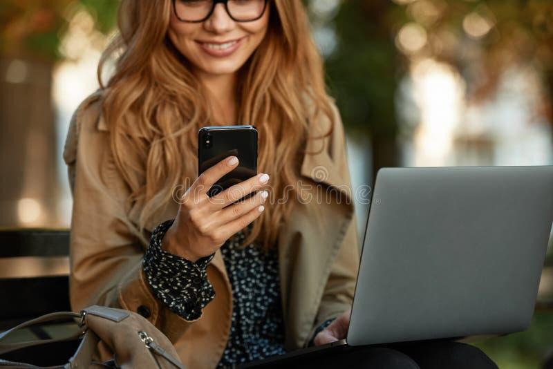 Foto de la muchacha elegante que usa el teléfono móvil y el ordenador portátil mientras que se sienta en banco en callejón ilumin fotografía de archivo