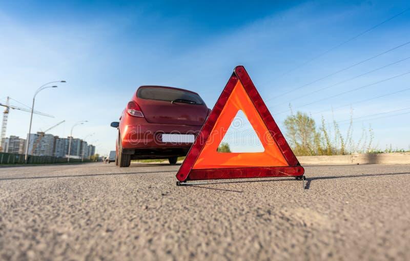Foto de la muestra roja del triángulo en el camino al lado del coche quebrado imágenes de archivo libres de regalías