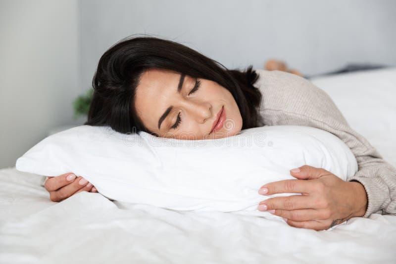 Foto de la mujer adulta 30s que duerme, mientras que miente en cama con el lino blanco en casa fotos de archivo libres de regalías