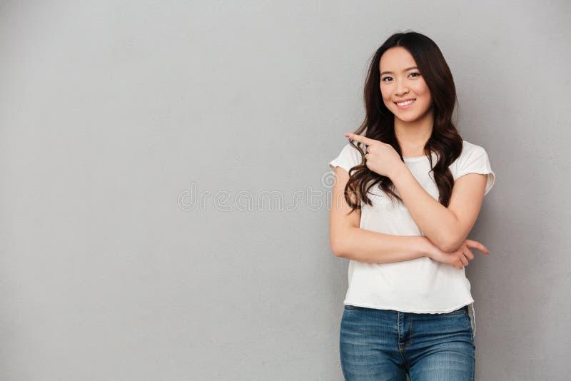Foto de la mujer afable asiática en la presentación casual de la camiseta y de los vaqueros foto de archivo libre de regalías
