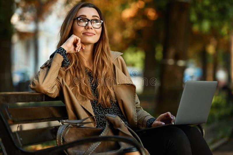 Foto de la mujer afable que trabaja en el ordenador portátil mientras que se sienta en banco en callejón iluminado por el sol foto de archivo