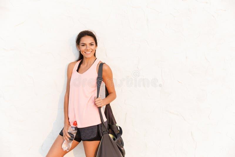 Foto de la mujer atlética en ropa de deportes con el bolso deportivo, sonrisa imagen de archivo
