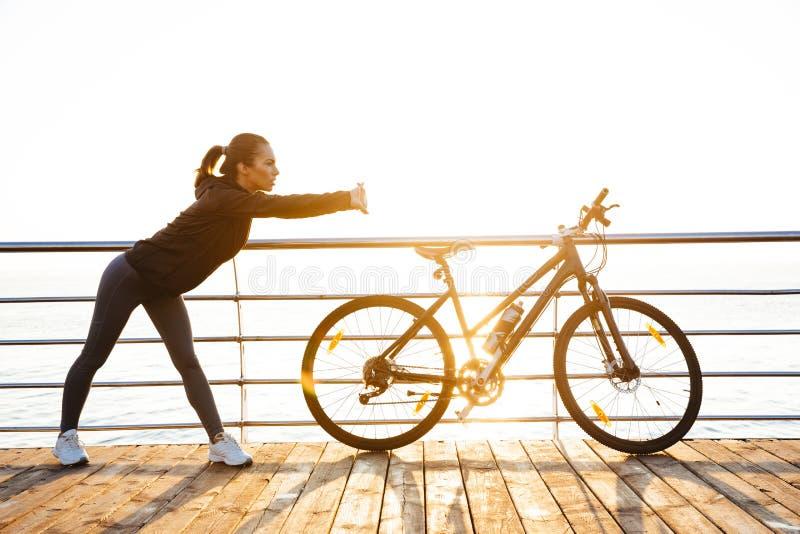 Foto de la mujer atlética que hace estirando ejercicios, mientras que se coloca cerca de la bicicleta al aire libre durante salid imagen de archivo libre de regalías