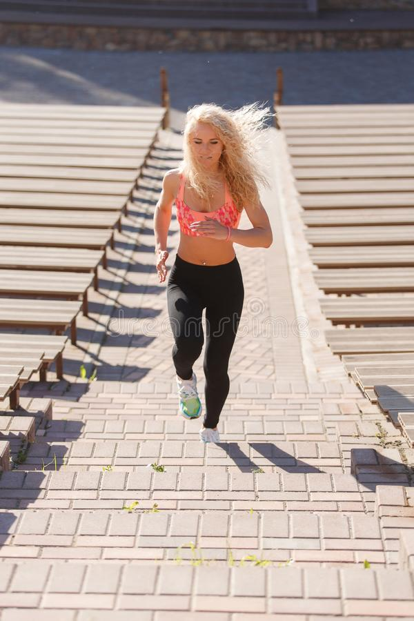 Foto de la mujer atlética rizado-cabelluda que corre a través de parque entre bancos fotografía de archivo