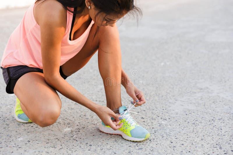 Foto de la mujer atlética 20s en el chándal que se pone en cuclillas, y atando él fotos de archivo libres de regalías