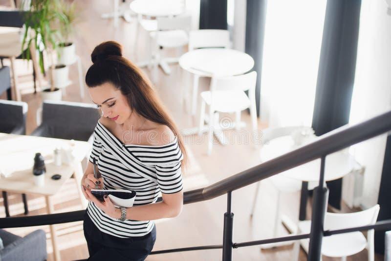 Foto de la mujer bonita que hace notas y que piensa sobre un tema mientras que se coloca en alguna cafetería con su ordenador por fotografía de archivo libre de regalías
