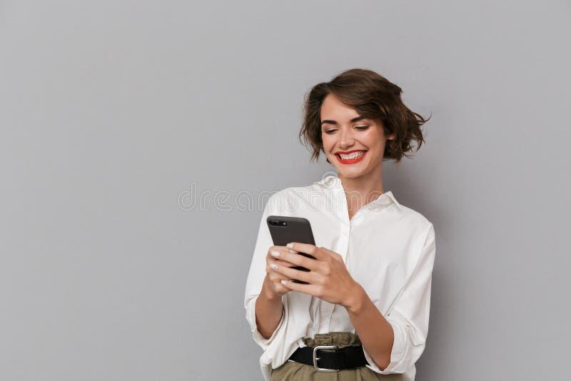 Foto de la mujer caucásica 20s que sonríe y que sostiene el teléfono móvil, i imagen de archivo libre de regalías