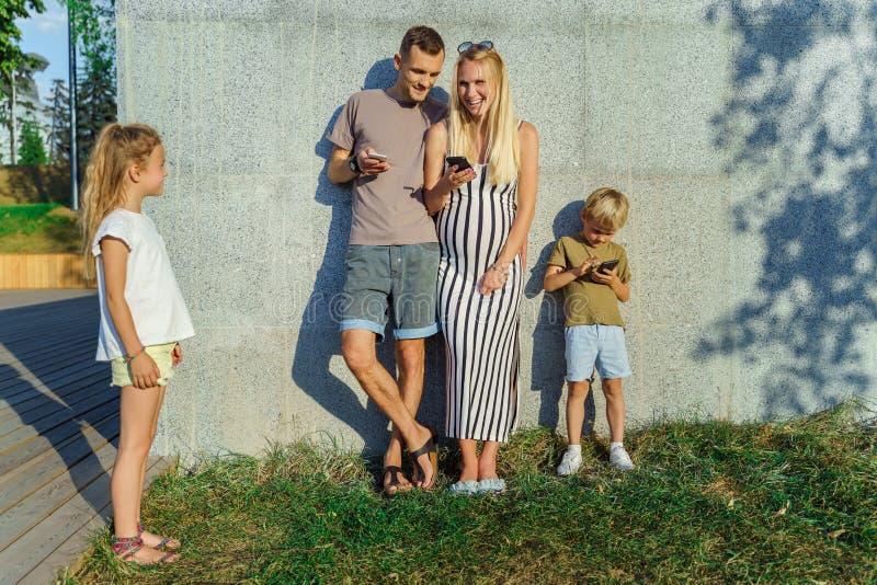 Foto de la mujer, del hombre y del hijo con los teléfonos en sus manos e hijas al lado del muro de cemento afuera imagenes de archivo