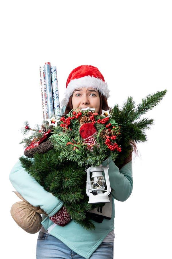 Foto de la mujer en el casquillo de Papá Noel con el árbol de navidad, linterna, papel de embalaje en manos fotografía de archivo