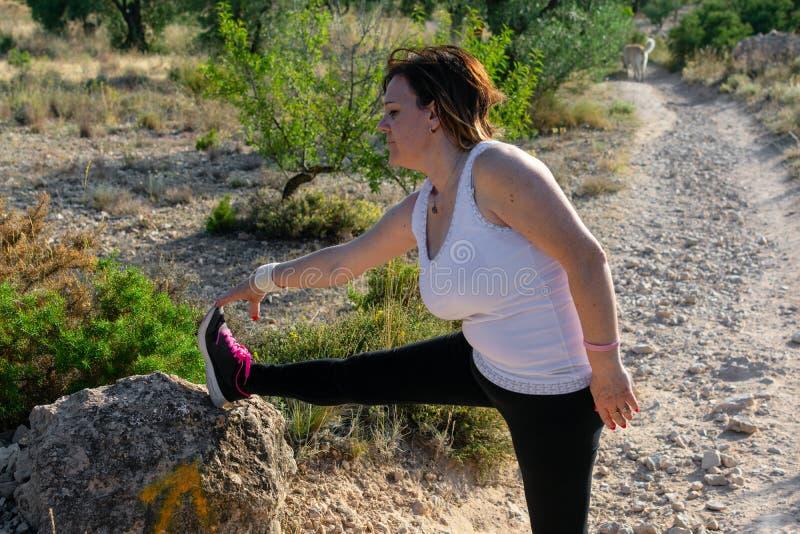 Foto de la mujer envejecida media en la ropa de los deportes que practica estirar al aire libre fotos de archivo libres de regalías
