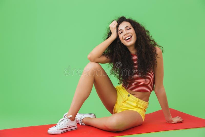 Foto de la mujer europea 20s de la aptitud que sonríe y que se sienta en la estera de la yoga durante aeróbicos fotos de archivo libres de regalías