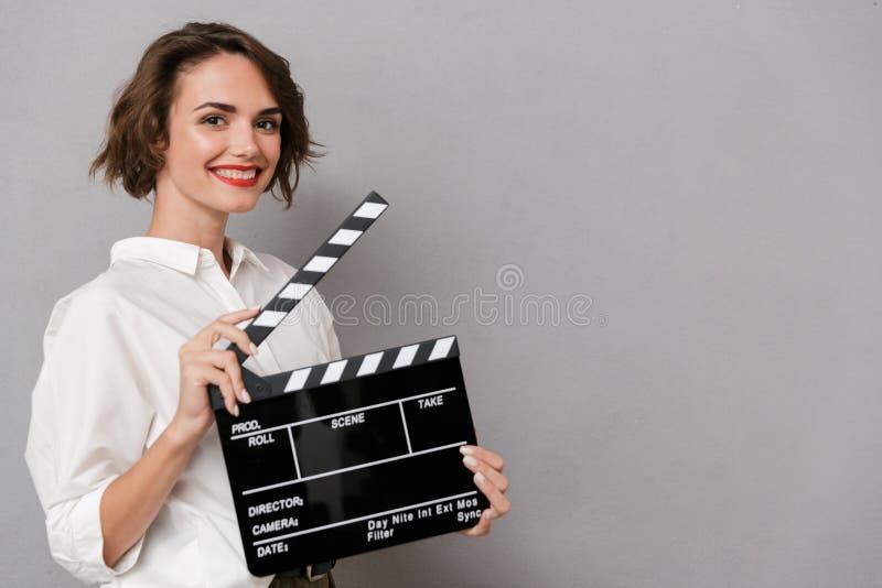 Foto de la mujer europea 20s que sonríe y que sostiene clapperboa negro foto de archivo libre de regalías