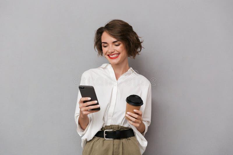 Foto de la mujer europea 20s que sostiene el café para llevar y que usa el ce fotos de archivo libres de regalías