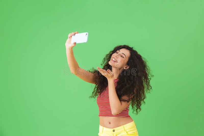 Foto de la mujer feliz que sonríe y que usa el teléfono celular para el selfie sobre fondo verde imágenes de archivo libres de regalías