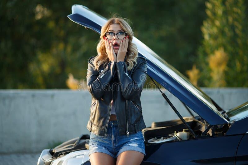 Foto de la mujer frustrada en vidrios cerca del coche quebrado con la capilla abierta imagen de archivo