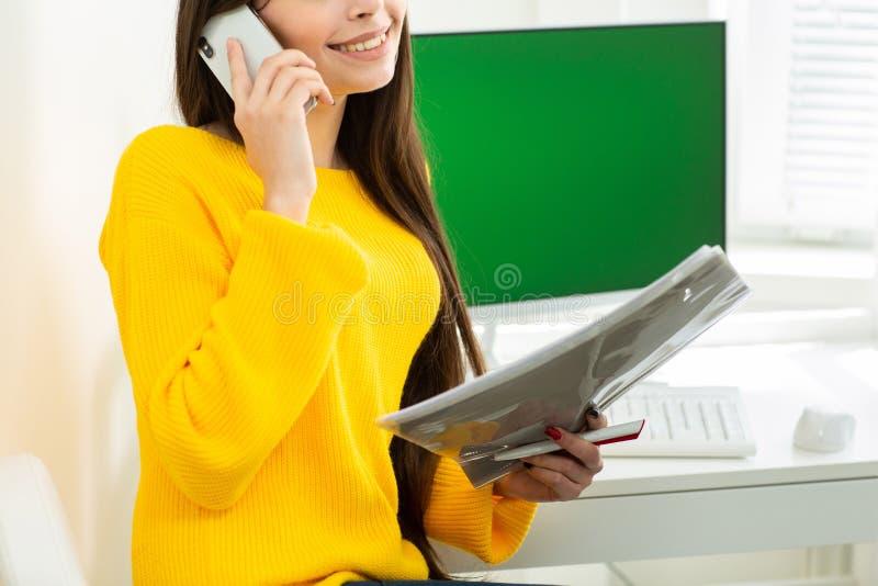 Foto de la mujer, hablando en el tel?fono y leyendo documentos en oficina Pantalla verde en el fondo imágenes de archivo libres de regalías