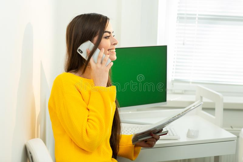 Foto de la mujer, hablando en el tel?fono y leyendo documentos en oficina Pantalla verde en el fondo fotografía de archivo