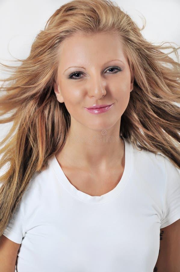 Foto de la mujer hermosa con el retrato en blanco del estudio de la camiseta fotografía de archivo