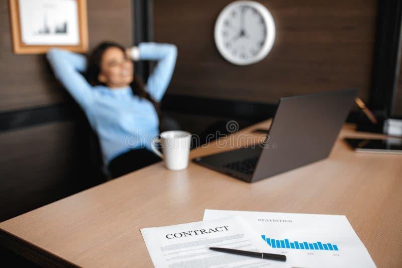 Foto de la mujer joven bonita del encargado que se relaja después de trabajar con el ordenador portátil en oficina moderna Celebr foto de archivo libre de regalías