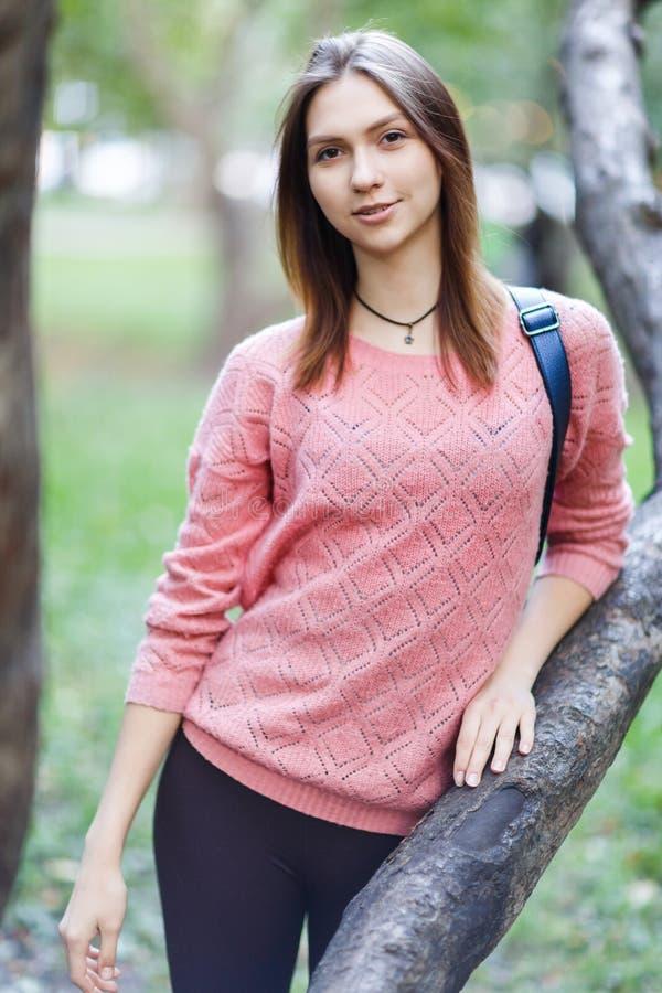 Foto de la mujer joven en chaqueta rosada en paseo imagen de archivo libre de regalías