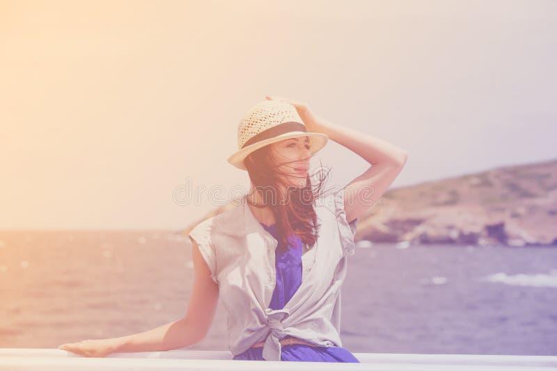 Foto de la mujer joven hermosa en el barco delante del mar y de i imagenes de archivo