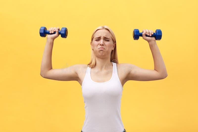Foto de la mujer joven seria de los deportes hacer ejercicios con pesas de gimnasia aislada sobre fondo amarillo de la pared fotografía de archivo