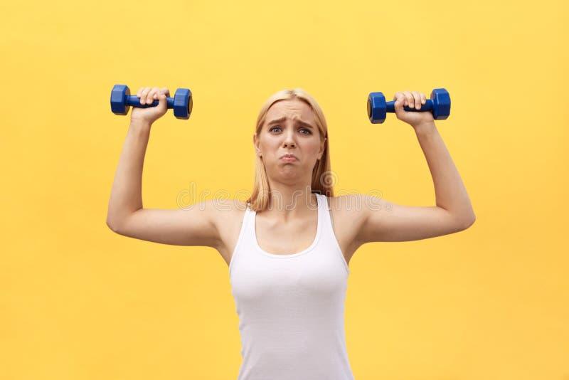 Foto de la mujer joven seria de los deportes hacer ejercicios con pesas de gimnasia aislada sobre fondo amarillo de la pared imagenes de archivo