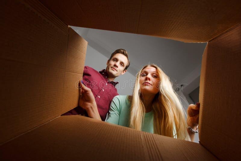 Foto de la mujer joven y del hombre que miran dentro de la caja de cartón fotografía de archivo libre de regalías