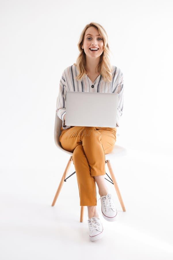 Foto de la mujer linda cauc?sica que lleva la ropa casual que sonr?e en la c?mara y que usa el ordenador port?til mientras que se imagen de archivo