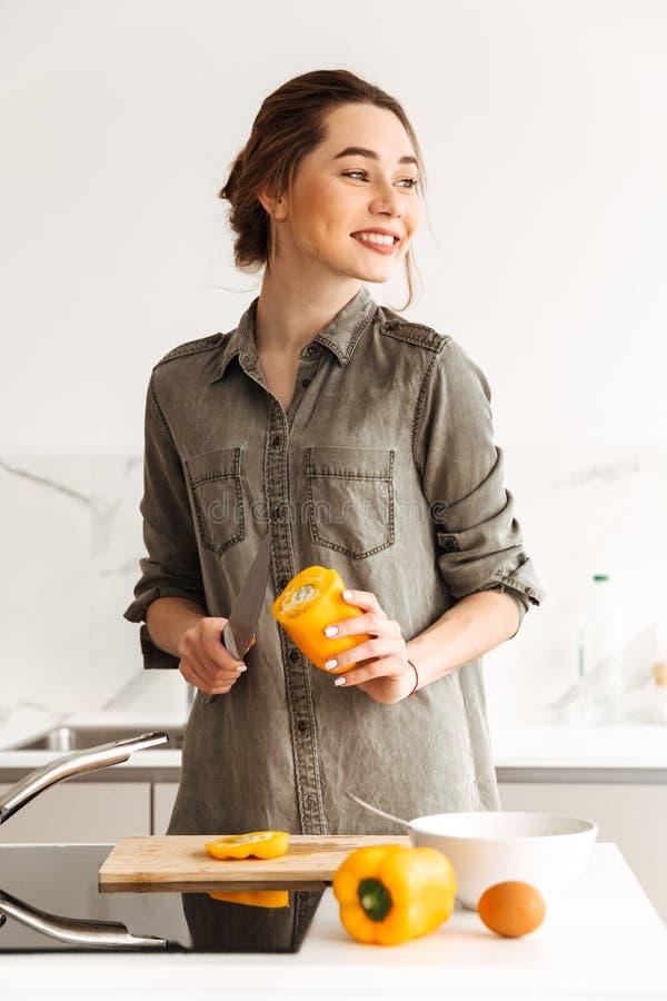 Foto de la mujer preciosa y sana que cocina la cena en el apartamento, w fotografía de archivo
