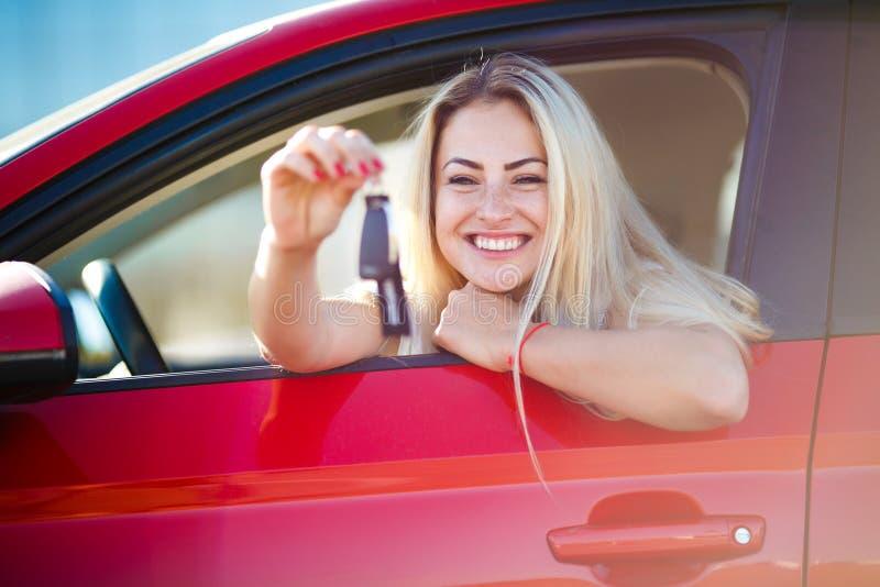 Foto de la mujer rubia hermosa con las llaves que se sientan en coche rojo con la ventana abierta fotos de archivo libres de regalías
