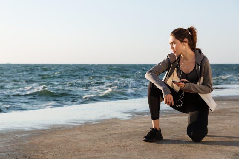 Foto de la mujer sana joven del deporte que se sienta en rodilla, considerándose smar fotografía de archivo libre de regalías