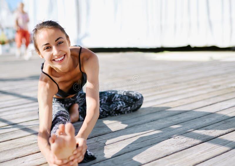 Foto de la mujer sonriente joven hacer ejercicios de la yoga en un embarcadero de madera fotografía de archivo