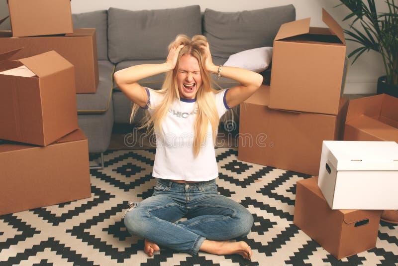 Foto de la mujer trastornada que se sienta en piso entre las cajas de cartón foto de archivo libre de regalías