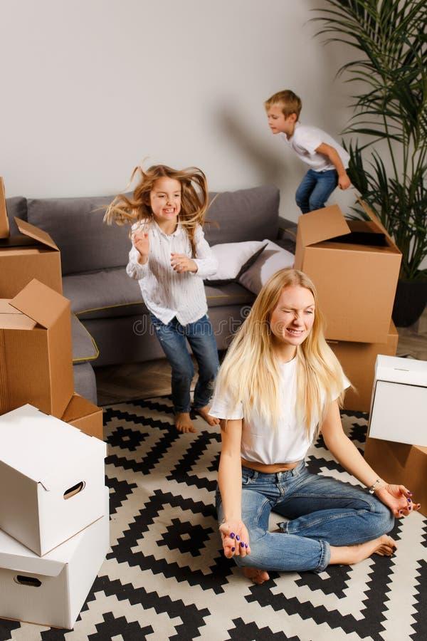 Foto de la mujer trastornada que se sienta en piso entre las cajas de cartón y muchacho y muchacha fotografía de archivo