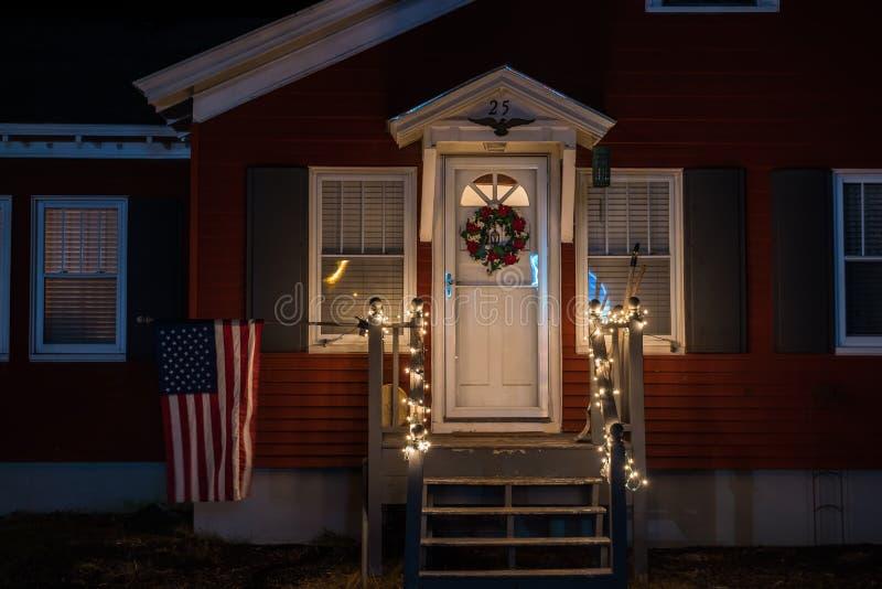 Foto de la noche del pórtico de una pequeña casa simple adornada con guirnaldas de la Navidad y una guirnalda La bandera de Améri imagen de archivo libre de regalías