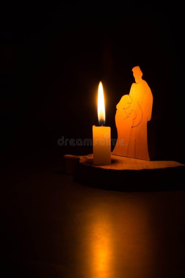 Foto de la noche de la familia santa cerca de la luz de una vela fotografía de archivo