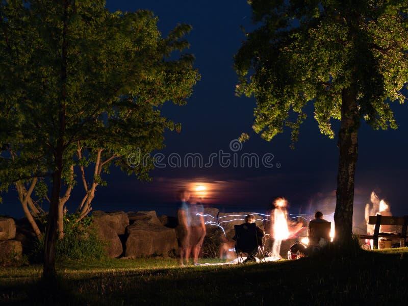 Foto de la noche de una compañía alrededor de una hoguera imagen de archivo