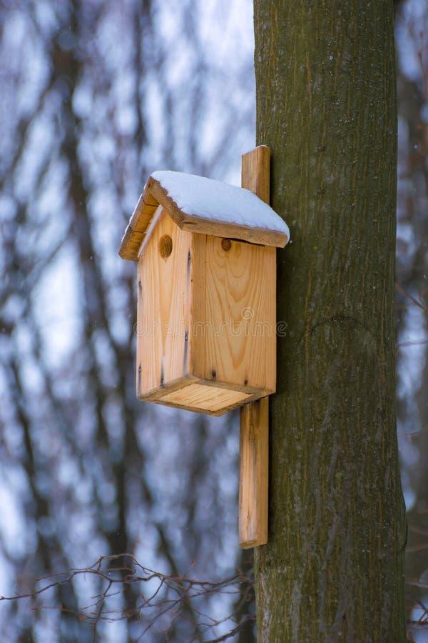 Foto de la pajarera de madera en el bosque en invierno imagenes de archivo