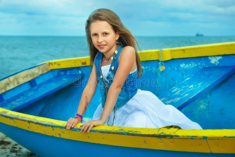 Pequeña muchacha linda en un barco en la playa, día de vacaciones. imagenes de archivo