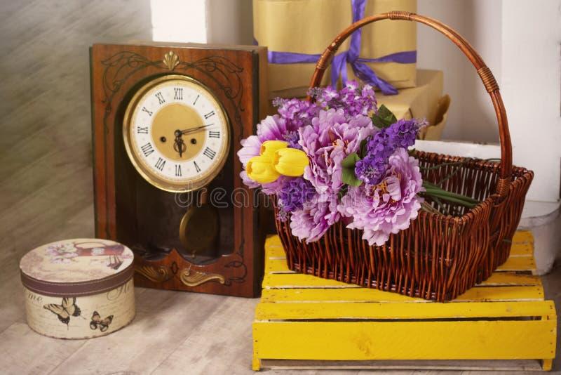 Foto de la primavera con las flores retras del reloj en una caja de la cesta fotos de archivo libres de regalías