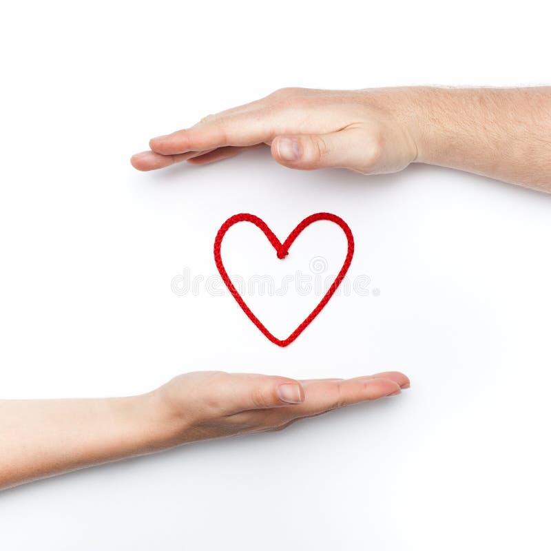 Foto de la relación con dos manos con el corazón rojo imagen de archivo