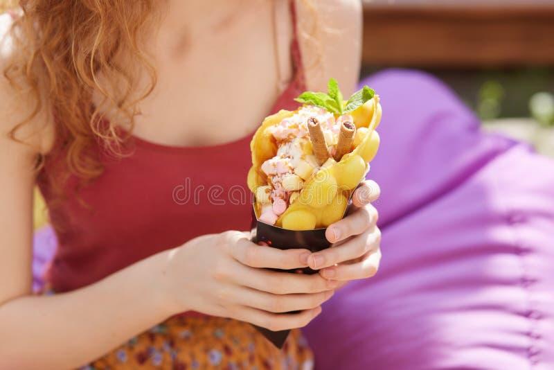 Foto de la señora delgada con la falda superior del pelo rizado, colorida roja que lleva, sentándose en el beanbag violeta al air fotografía de archivo libre de regalías
