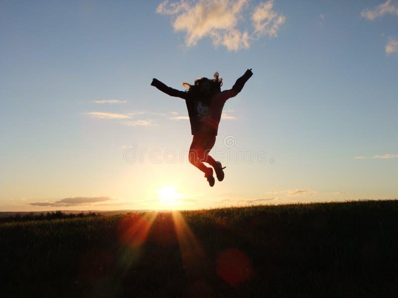Foto de la silueta de un campo de Person Jumping Nearby Green Grass durante hora de oro foto de archivo