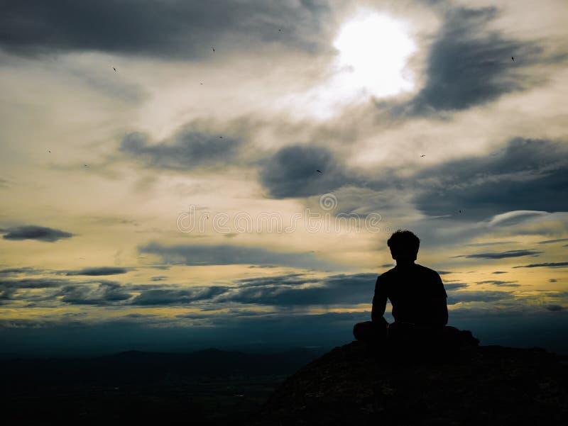 Foto de la silueta de la sentada turística en el acantilado rocoso en la montaña de Khao Luang en el parque nacional de Ramkhamha fotografía de archivo libre de regalías