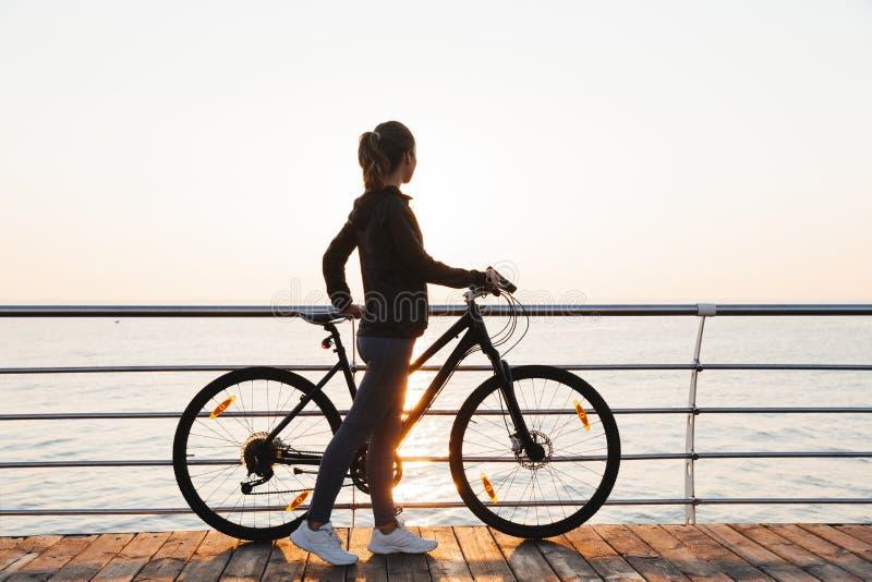 Foto de la situación atlética de la mujer con la bicicleta en paseo marítimo, durante salida del sol sobre el mar fotos de archivo