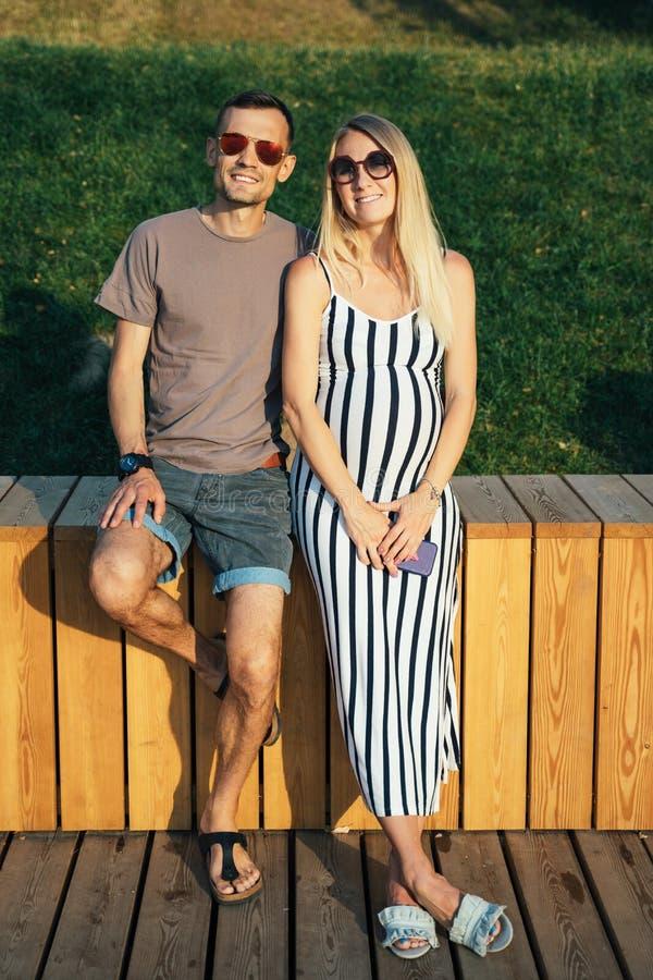 Foto de la situación de la mujer embarazada y del hombre cerca de la cerca de madera el día de verano foto de archivo libre de regalías