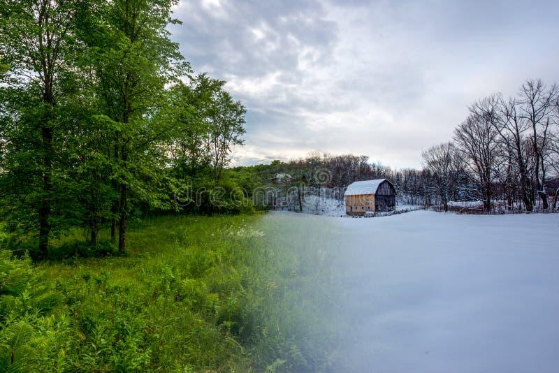 Foto de la transición a partir del verano al invierno del granero y de árboles en un campo foto de archivo